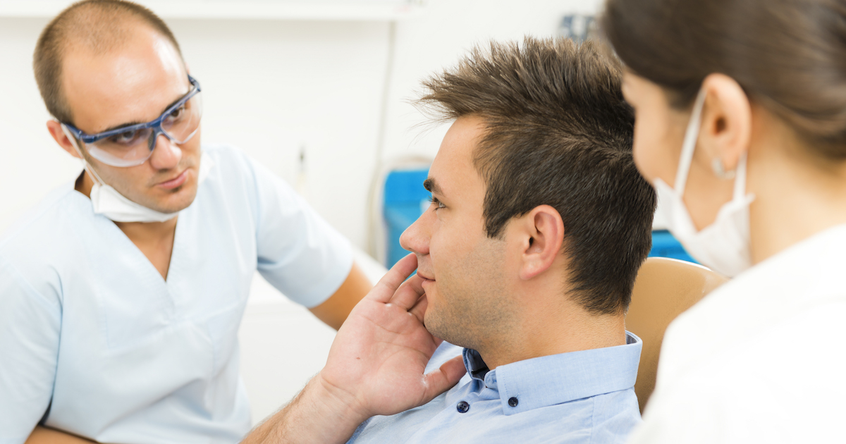 Patient upset by toothache, discussing with the dentists.